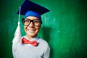 Joyful kid in eyeglasses and graduation hat looking at camera with smile