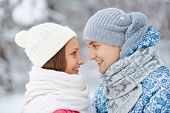 Young woman and man in winterwear looking at one another with smiles outside