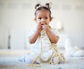 Portrait of a cute little girl playing with beads in isolation