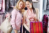 Two friendly females with shopping bags in department store