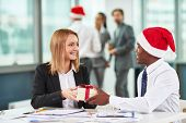 Portrait of African businessman giving Christmas present to Caucasian female colleague