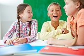 Cute schoolkids laughing at lesson of drawing