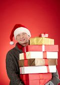 Portrait of generous Santa man with pile of giftboxes