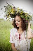 attractive girl in a meadow with a wreath