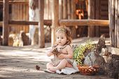 Girl playing with fir cones sitting on the ground.