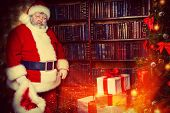 Tired Santa Claus stands by the fireplace with a bag of gifts. Christmas home decoration.