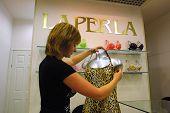KIEV, UKRAINE, 16 AUGUST 2003: A sales clerk checking a display at a La Perla shop in Kiev, Ukraine. La Perla is a luxury Italian women's clothing company specializing in lingerie.