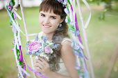 The beautiful bride on a swing under a tree