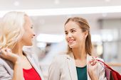 sale, consumerism and people concept - happy young women with shopping bags talking in mall