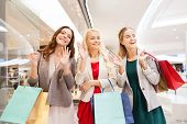 sale, consumerism and people concept - happy young women with shopping bags waving hands in mall