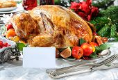 Roasted turkey on holiday table, empty tag and Christmas tree with ornaments