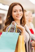 sale, consumerism and people concept - happy young women with shopping bags in mall
