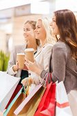 sale, consumerism and people concept - happy young women with shopping bags and coffee paper cup in mall