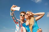 summer, vacation, holidays, technology and friendship concept - smiling couple with smartphone making selfie outdoors