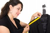 beautiful young woman tailor measuring a black suit