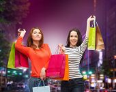 sale, friendship and people concept - two smiling teenage girls with shopping bags over night city background