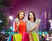 sale, friendship and people concept - two smiling teenage girls with shopping bags and cash money over night city background