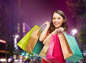 happiness, consumerism, sale and people concept - smiling young woman with shopping bags over night city background