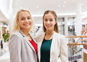 sale, consumerism and people concept - happy young women in mall or business center