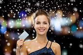 shopping, wealth, money, christmas and people concept - smiling woman in evening dress holding credit card over night lights and snow background
