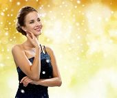 people, holidays, christmas  and glamour concept - smiling woman in evening dress over black background over yellow lights and snow background
