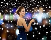 party, drinks, holidays, people and christmas concept - smiling woman in evening dress holding cocktail over night lights and snow background