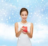 christmas, holidays, presents, wedding and people concept - smiling woman in white dress holding red gift box over blue cloudy sky and snow background