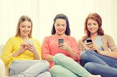 friendship, technology and internet concept - three smiling teenage girls with smartphones at home