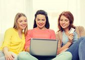 friendship, money, technology and internet concept - three smiling teenage girls with laptop computer and credit card at home