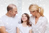 family, childhood, communication, people and home concept - smiling parents with little girl talking at home