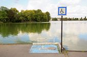 Place for wheelchair, in front of a pond.