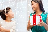 holidays, presents, christmas, x-mas concept - happy mother and child girl with gift box over snowy background