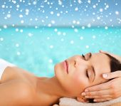 beauty, health, holidays, people and spa concept - beautiful woman in spa salon getting face or head massage over sky and sea with snowflakes background