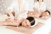 beauty, health, holidays, people and spa concept - happy couple with closed eyes lying getting back massage in spa salon