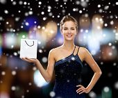 people, advertisement, christmas holidays and sale concept - smiling woman with white blank shopping bag over night lights and snow background