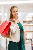 sale, consumerism and people concept - happy young woman with shopping bags in mall
