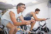 Fit people working out on the exercise bikes at the gym