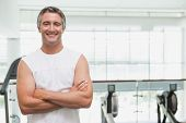 Fit man smiling at camera in fitness studio at the gym