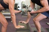 Side view mid section of a couple exercising with dumbbells in the gym