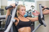 image of physique  - Portrait of a fit young woman using fitness machine at the gym - JPG