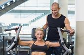 Smiling male trainer assisting woman on fitness machine at the gym