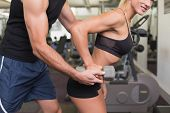 Side view of a male trainer assisting woman with dumbbell in the gym