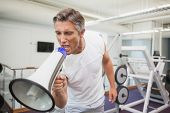 Angry personal trainer shouting through megaphone at the gym