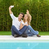 A couple sitting by the pool taking a selfie with the smart phone