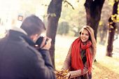A picture of a beautiful woman posing to the camera in the park in autumn