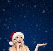 Beautiful woman in Christmas cap gestures palm up, isolated on blue snowfall background