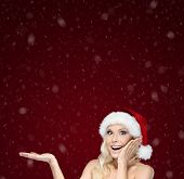 Beautiful woman in Christmas cap gestures palm up, on purple background
