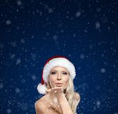 Beautiful woman in Christmas cap blows kiss, winter background