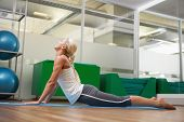 Full length side view of a young woman stretching her back in fitness studio