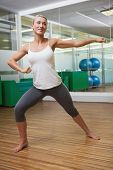 Portrait of a smiling young woman doing power fitness exercise at yoga class